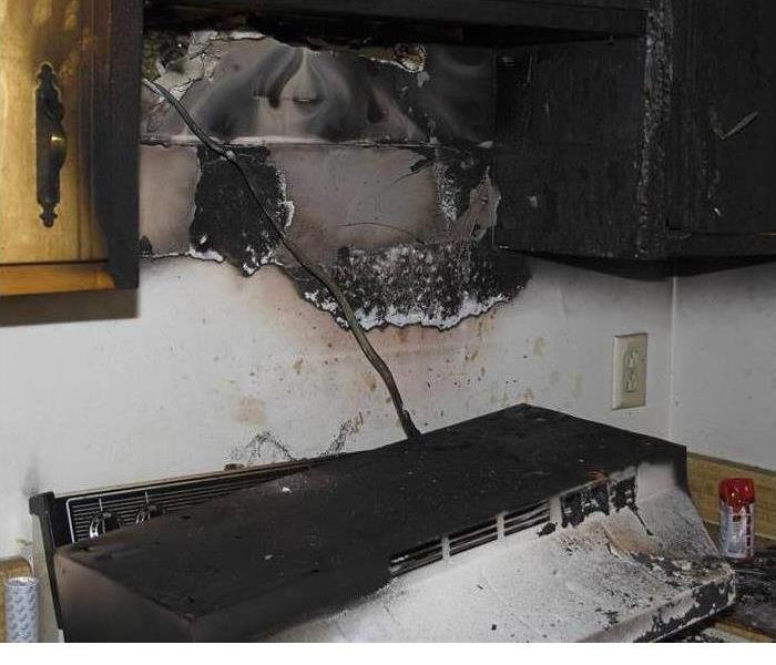 this is a picture of a burnt exhaust fan that fell onto a stove  the area around it is charred and cabinets are burnt